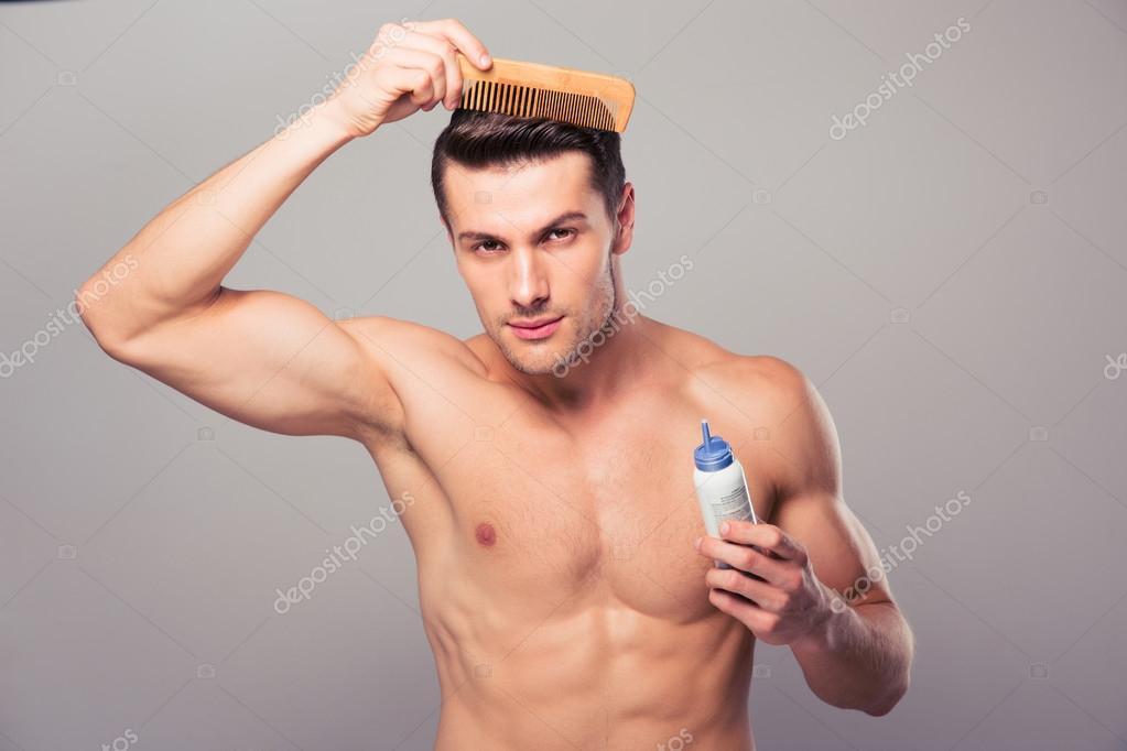 Aplicar spray de cabello para pelo hombre joven sobre fondo gris. Mirando a cámara — Foto de Vadymvdrobot