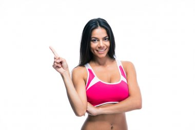Smiling fitness woman pointing finger up