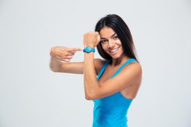 Smiling fitness woman pointing on fitness tracker