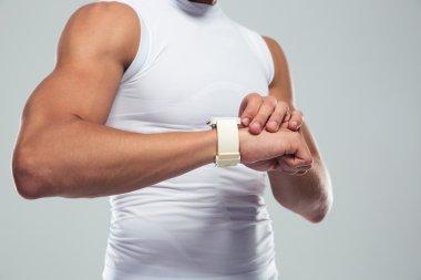 Closeup portrait of a muscular man using smartwatch