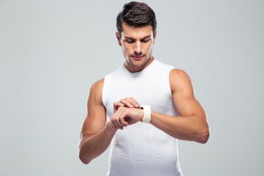 Handsome fitness man using smart watch