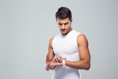 Handsome sports man using smart watch