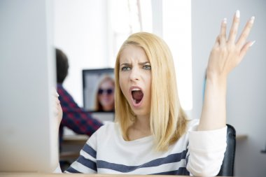 Shocked young woman working on computer