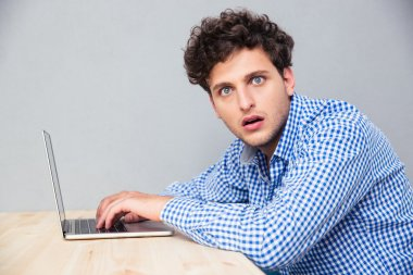 Shocked man sitting at the table with laptop