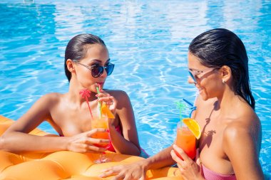 Girls drinking cocktails in swimming pool