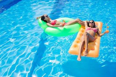 Girls resting on air mattress in swimming pool