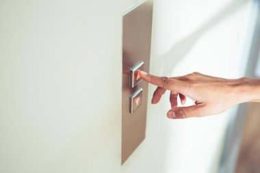 Female finger pushing elevator button