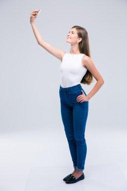 Happy female teenager making selfie photo on smartphone