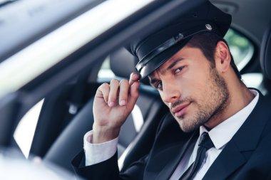 Handsome male chauffeur sitting in a car