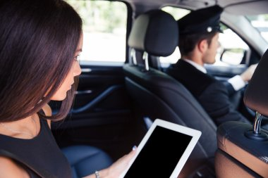 Woman using tablet computer in taxi