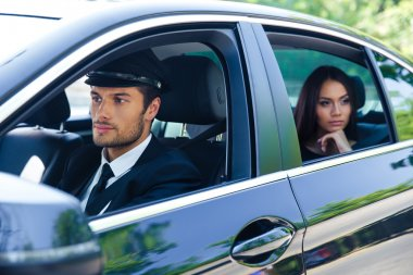 Woman riding in a car with chauffeur
