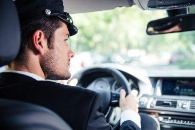 Male chauffeur riding car
