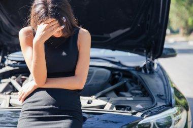 Woman standing near broken car