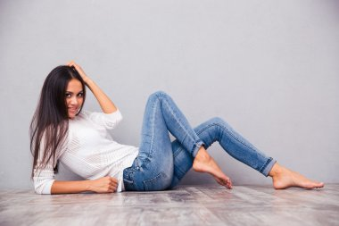 Smiling attractive woman lying on the floor