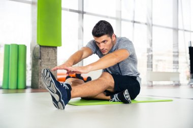 Man doing stretching exercises at gym