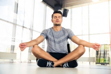 Man meditating in fitness gym