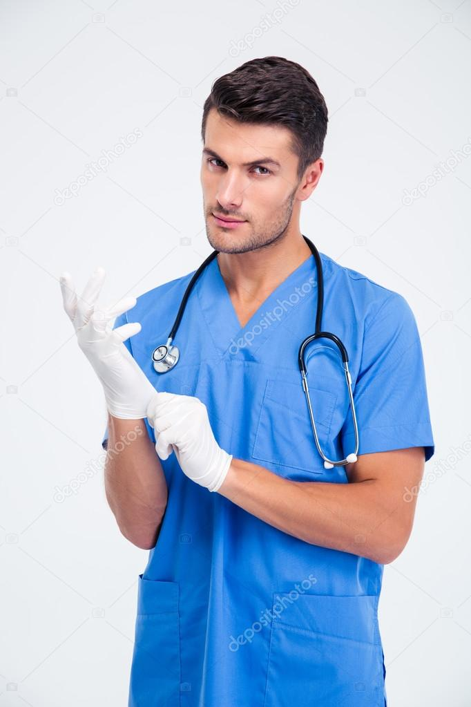 Handsome male doctor putting gloves — Stock Photo © Vadymvdrobot ...