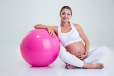 Pregnant woman sitting on the floor with fitness ball