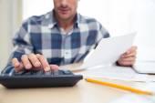 Fotografie Man with calculator checking bills