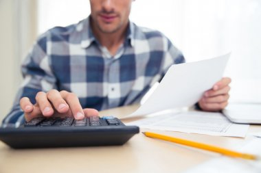 Man with calculator checking bills
