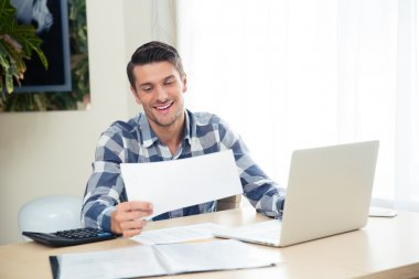 Man checking bills on the tablet at home