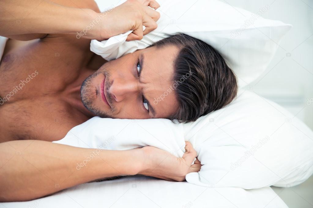 homme allong dans le lit avec oreiller sur la t te photographie vadymvdrobot 84981988. Black Bedroom Furniture Sets. Home Design Ideas
