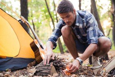 Handsome man kindle bonfire
