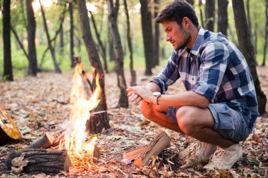 Man sitting near bonfire in the forest