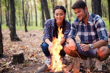 Couple and bonfire in the forest