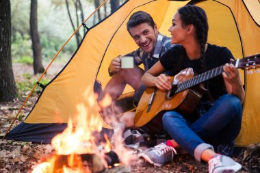 Couple sitting with guitar near bonfire