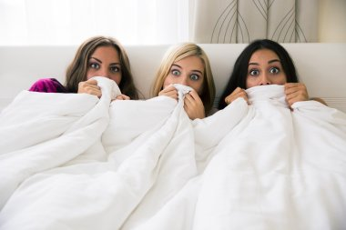 Scared girlfriends covering their face with blanket
