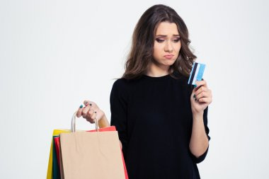 Sad woman holding shopping bags and bank