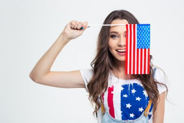 Smiling woman covering her eye with USA flag
