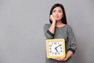 """Картина, постер, плакат, фотообои """"азиатская девушка ждет и держит большие часы """", артикул 87494682"""