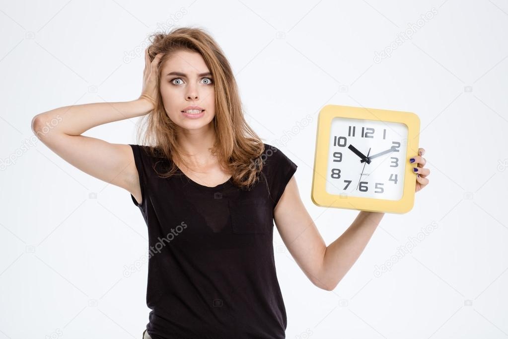 Nervous woman holding wall clock