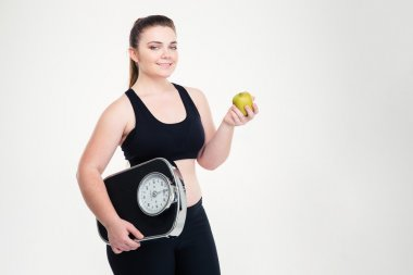 Fat woman holding weighing machine and apple