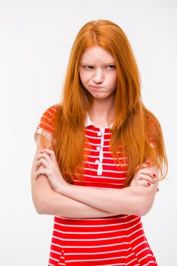 Cute offended girl standing with hands crossed