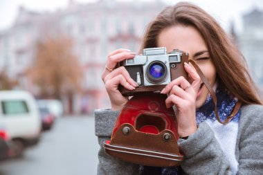 Woman making photo on retro camera