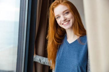 Cheerful pretty girl with red hair looking camera and smiling