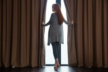 Relaxed  woman opening curtains and looking back