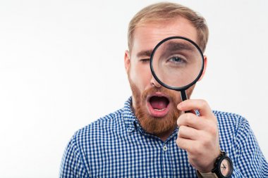 Man looking through magnifying glass at camera