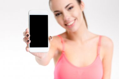 Happy pretty fitness girl showing cellphone with blank screen