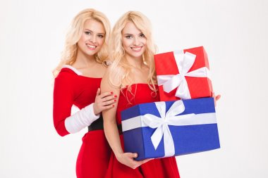 Two beautiful sisters twins in santa claus costumes holding gifts