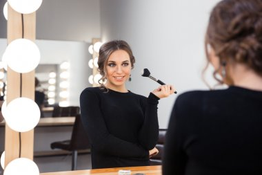 Happy woman applying cosmetic with brush