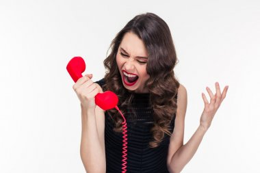 Crazy raged retro styled female shouting in red telephone receiver