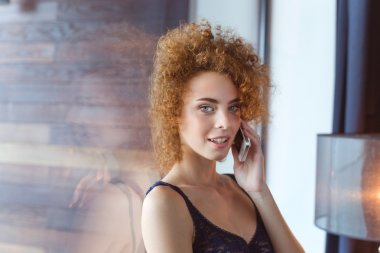 Seductive relaxed young woman talking on mobile phone