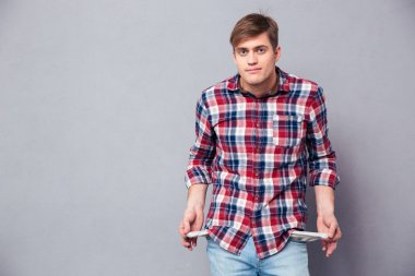 Poor handsome young man in checkered shirt showing empty pockets