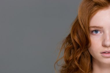 Half face of redhead curly woman with beautiful long hair