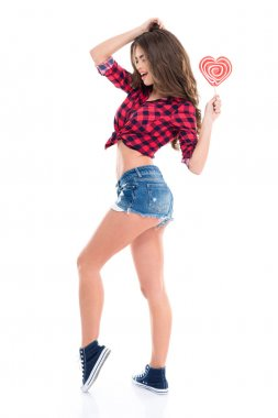 Attractive cheerful young woman  with heart shaped candy