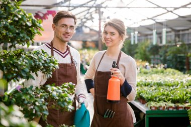 Happy gardeners holding watering can and pulveriser for spraying flowers